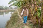 Farmer walking along a path near the lake
