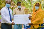 Sanasa insurance representative handing over insurance payout to farmers