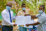 Sanasa insurance representative handing over insurance payout to farmers at a ceremony held in the village of Galenbindunuwewa